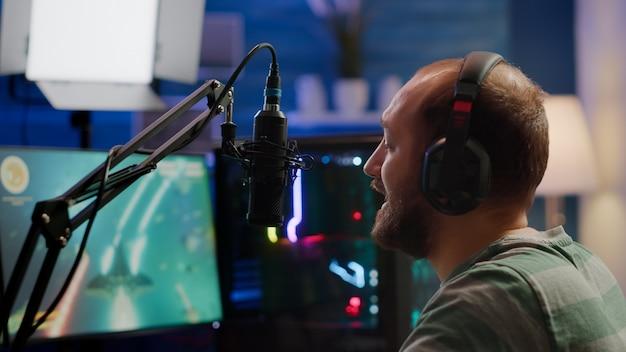 スペースシューティングトーナメント中に他のプレイヤーとマイクに向かって話しているストリーマーの男。プロのヘッドフォンとストリームチャットを使用したオンラインストリーミングサイバーパフォーマンスビデオゲームの競争