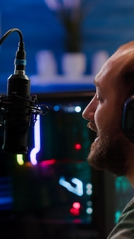 Человек-стример разговаривает в микрофон с другими игроками во время турнира по космической стрельбе. онлайн-стриминговые соревнования по компьютерным играм с использованием профессиональных наушников и потокового чата