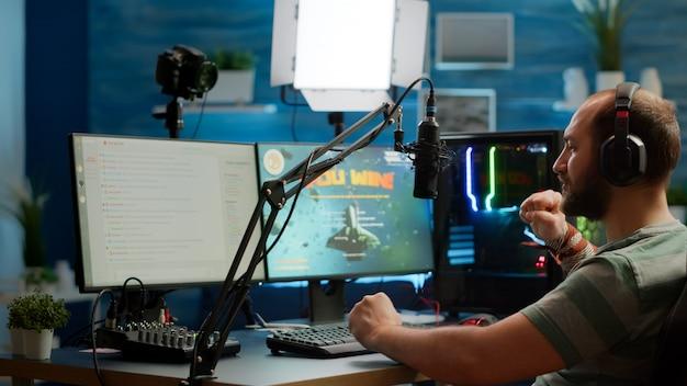 複数のプレーヤーとヘッドフォンで話し、ビデオゲームの競争に勝つストリーマーの男。ゲームルームから強力なコンピューターで新しいグラフィックスを使用してオンラインビデオゲームをストリーミングするプロのゲーマー