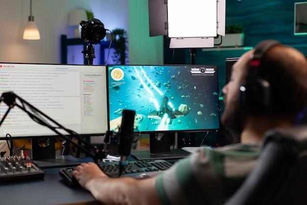 비디오 게임을 하고 스트리밍 공개 채팅에서 팀원들과 이야기하는 스트리머. 전문 장비를 사용하여 가정의 게임룸에서 강력한 컴퓨터로 사이버 수행