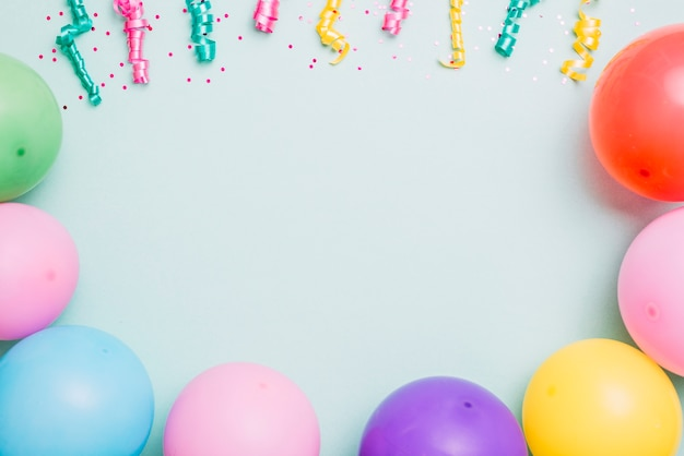Streamers and colorful balloons on blue backdrop with space for text