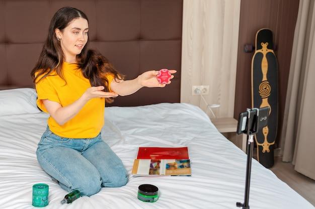 Стриминг и видеоблог. женский видеоблогер транслирует видео в реальном времени на смартфоне, показывая косметику, сидящую на кровати.