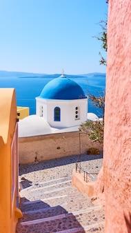 그리스 산토리니 섬의 이아 마을에 있는 바다 옆에 파란색 돔이 있는 거리와 그리스 정교회
