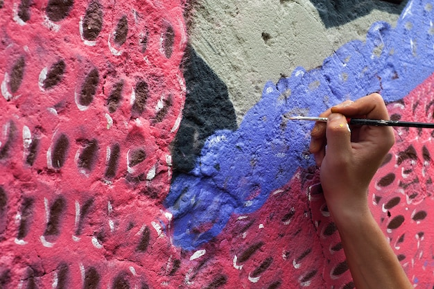 Street artist draws colorful graffiti on the concrete wall