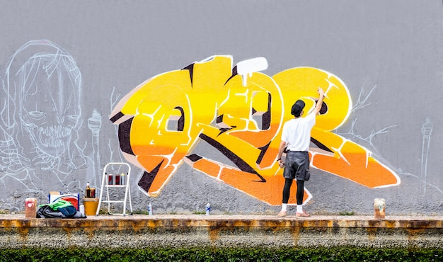 Street artist painting colored graffiti on public space wall