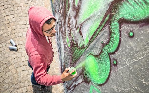 Уличный художник, рисующий красочные граффити на общей стене - высокий угол обзора