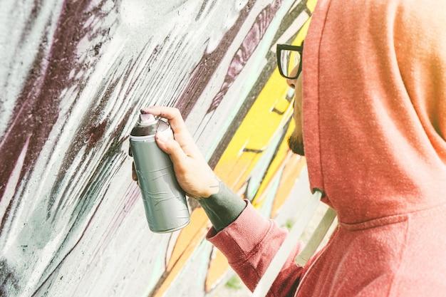 Уличный художник рисует граффити цветным баллончиком на стене