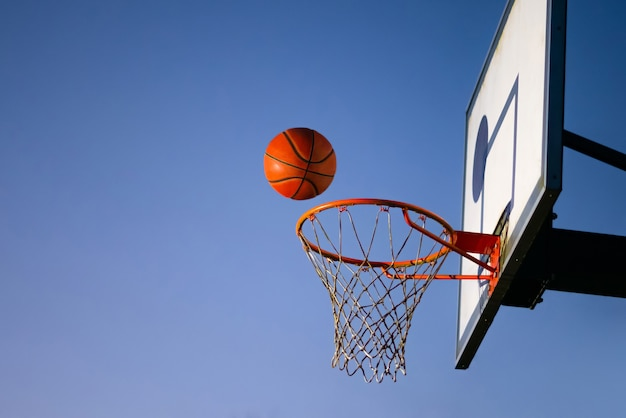 Мяч уличного баскетбола падает в кольцо на открытом воздухе.