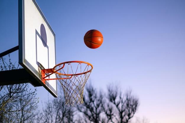 Мяч уличного баскетбола падает в обруч