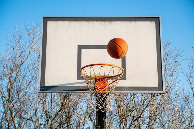 Мяч уличного баскетбола падает в обруч.