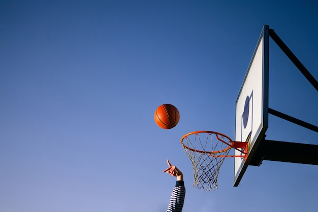 Уличный баскетболист, бросающий мяч в обруч