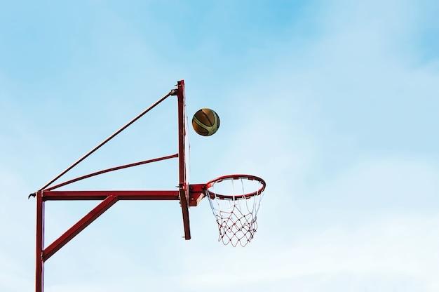 Доска кольца шара уличного баскетбола против неба.