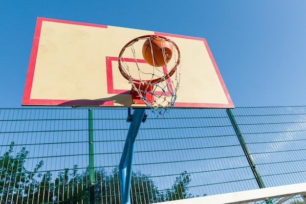 ストリートバスケットボール、バスケットボールリングとボールのクローズアップ