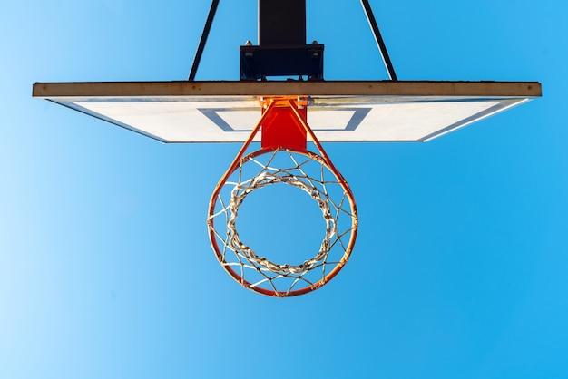 Уличное баскетбольное кольцо в солнечный день с голубым небом на поверхности.
