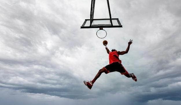 Уличный баскетболист делает мощный данк на площадке