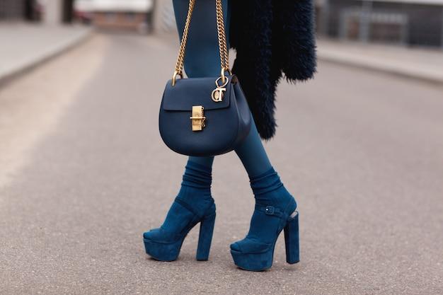 通り、明るいスタイル。かかとのハンドバッグと青い毛皮のコートの少女。詳細