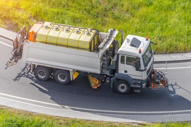 Подметально-уборочные машины перекачивают воду для мытья асфальтовой дороги.