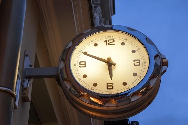 Уличные часы с подсветкой на фоне голубого ночного неба. центр вильнюса, литва.