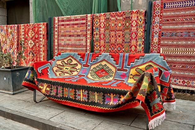 Уличный прилавок традиционных ковров на улице тбилиси.