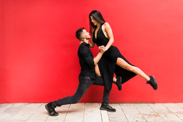 Street dancers performing tango against red bright wall