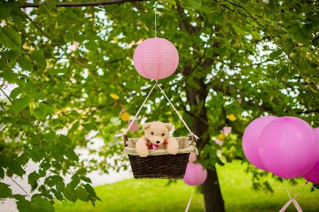 子供たちのパーティーのためのストリートデコレーション。緑豊かな公園の気球にテディベアが入ったバスケット。