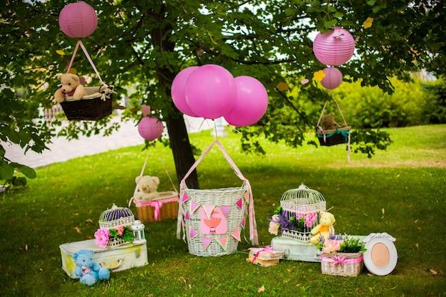 子供たちのパーティーのためのストリートデコレーション。緑の公園で風船と籐のバスケット。