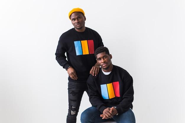 Уличная мода и концепция дружбы - два афро-американских молодых человека в черных стильных толстовках.