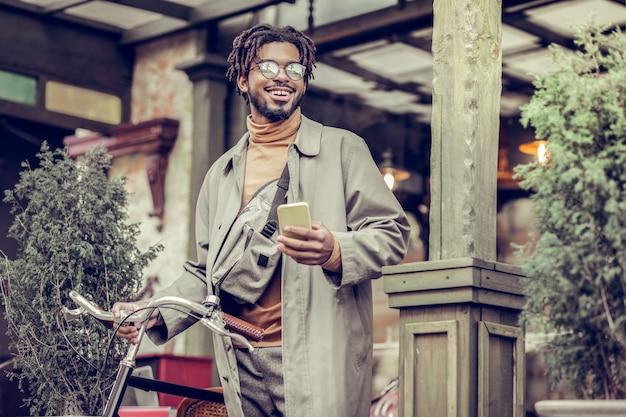 ストリートファッション。自転車の近くに立っている間彼の顔に笑顔を保つ陽気な青年
