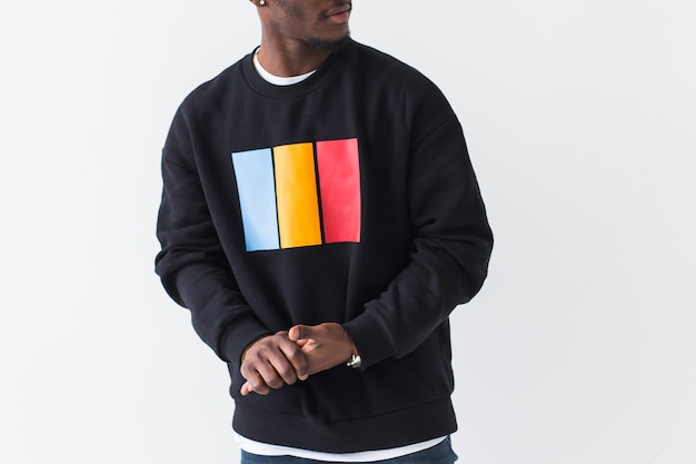 Street fashion concept - close-up of young handsome african man wearing sweatshirt against white