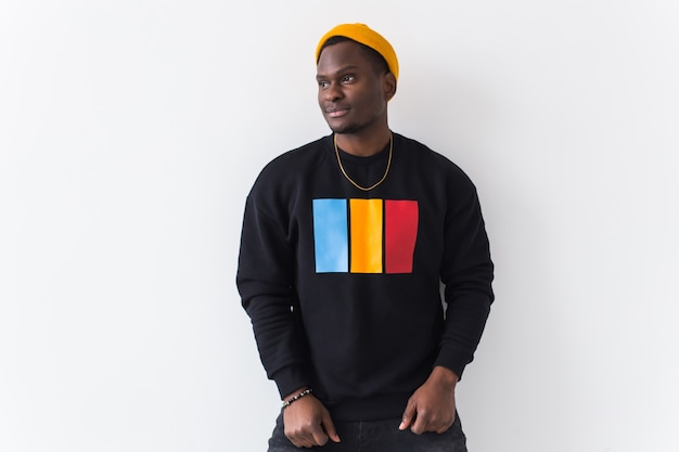 Street fashion concept - studio shot of young handsome african man wearing sweatshirt against white