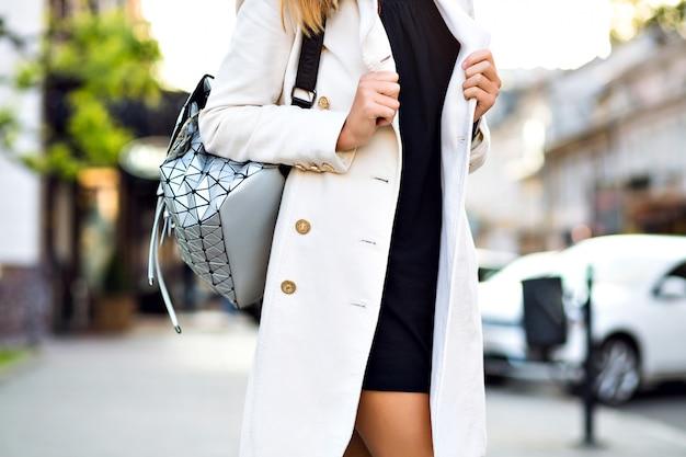 ストリートファッションの詳細、ヨーロッパの市内中心部でポーズをとる女性、秋の春、スタイリッシュなコート、珍しいバックパック、柔らかな色。