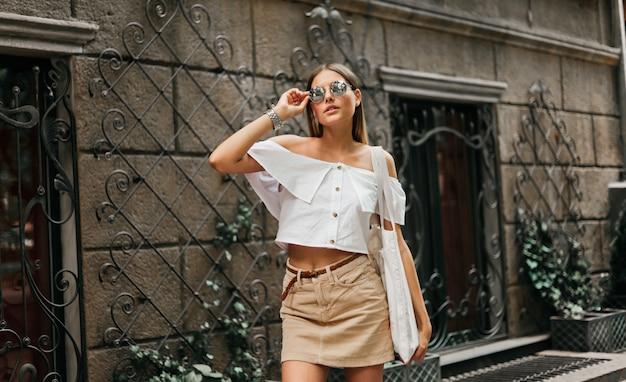 ストリートファッション。トレンディな服やサングラスの古い建築に対して屋外でポーズでファッショナブルなスタイリッシュな女性