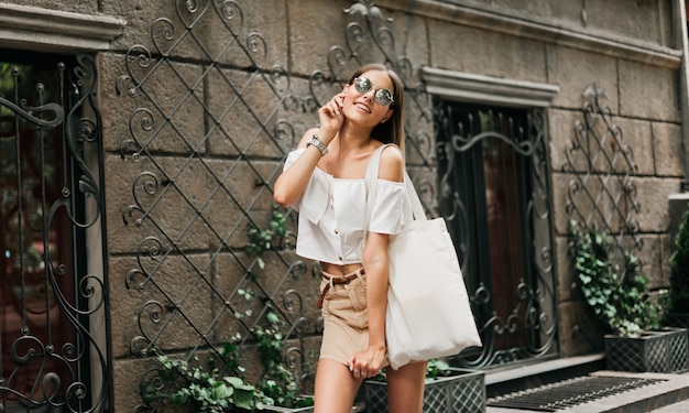 Street fashion. fashionable stylish woman in trendy clothes and sunglasses posing outdoors against old architecture