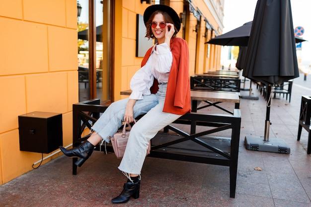 Уличная мода выглядит. удивительная стильная девушка в модном осеннем наряде позирует на улице