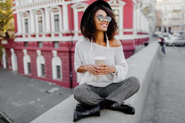 Уличная мода выглядит. стильная черная девушка сидит на мосту и держит чашку кофе