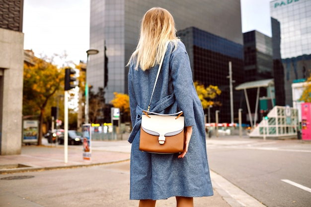 Ritratto di moda di strada di donna bionda che indossa cappotto blu e borsa alla moda, in posa indietro, turista di new york, stagione fredda primavera autunno.