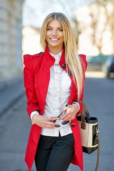 Street fashion portrait of  cute beautiful woman with bag
