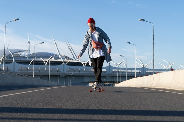 Street fashion and urban lifestyle hipster man in trendy casual clothes on longboard on city road