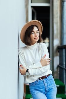 Street fashion woman wearing hat blue jeans wide hat transperent glasses on balcony