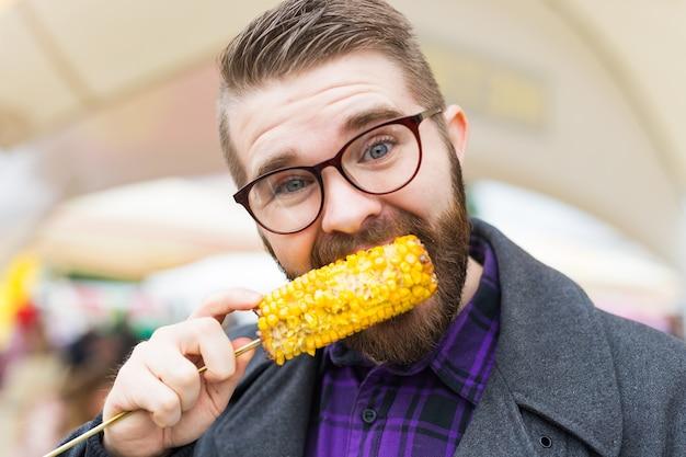 Уличная еда и концепция кухни - человек ест кукурузу на гриле. вегетарианская пища. полезные и вкусные овощи.