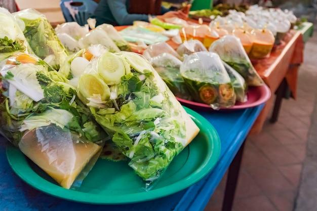 ラオス、ルアンパバーンの屋台の食べ物。食品は、市場近くの道端で販売する準備ができているビニール袋で梱包されています。