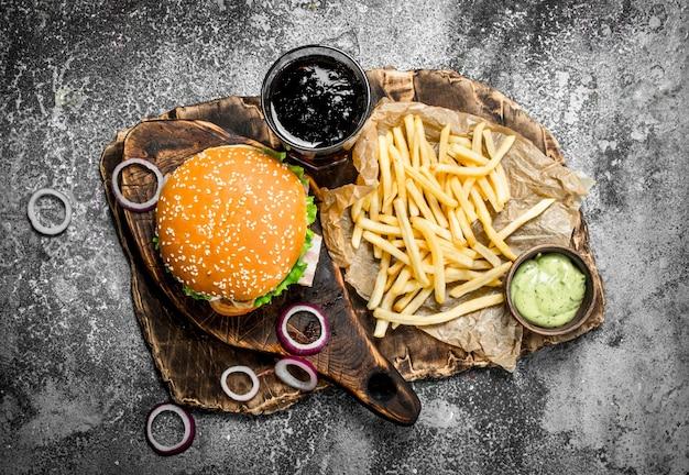 Уличная забегаловка. бургер с колой и картофелем фри. на деревенском столе.