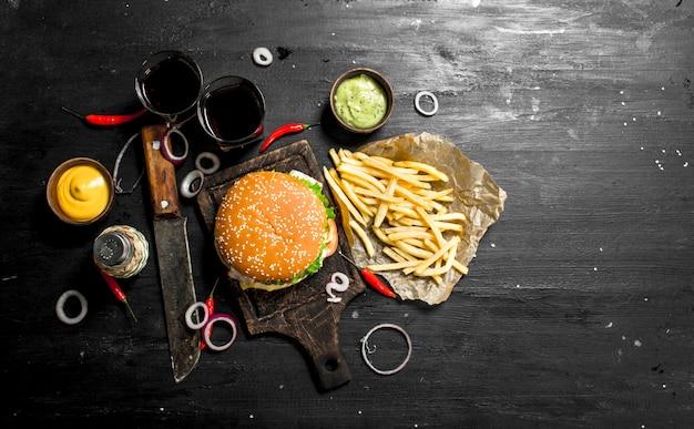 屋台の食べ物黒い黒板にコーラ、フライドポテト、ソースを添えた新鮮なハンバーガー