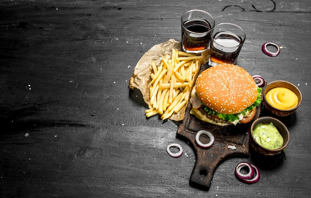 Street food fresh burger with cola, fries and sauces on the black chalkboard