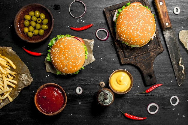 Street food fresh burgers with beef and vegetables on the black chalkboard