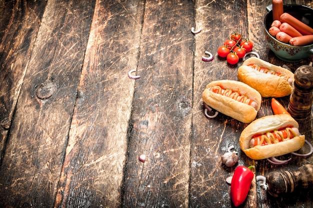 길거리 음식. 고추, 양파, 토마토 나무 테이블에 신선한 핫도그.