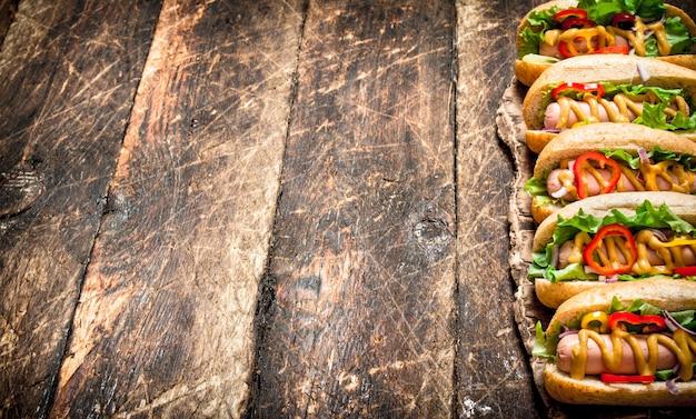 길거리 음식. 허브, 야채, 나무 테이블에 뜨거운 겨자와 핫도그.