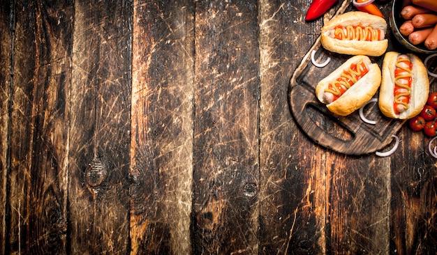 길거리 음식. 나무 테이블에 겨자와 토마토 소스 핫도그.