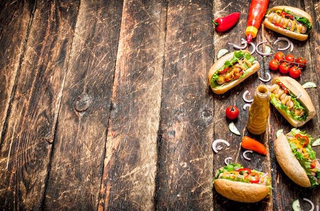 屋台の食べ物。マスタード、ホットソース、タマネギ、グリーンのホットドッグ。