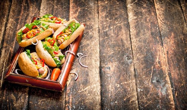 길거리 음식. 나무 테이블에 겨자, 핫 소스, onionnd 채소와 핫도그.